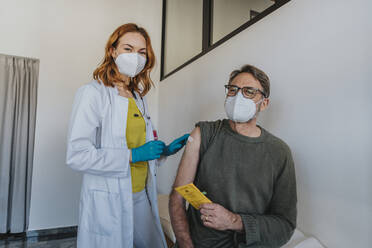 Doctor wearing protective face mask putting bandage while standing by male patient at examination room - MFF07438