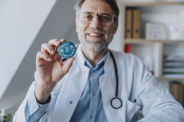 Smiling doctor holding peace sign gesture badge while standing at clinic - MFF07474