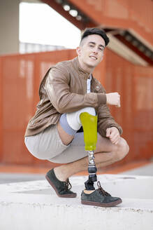 Caucasian young man, with a leg prosthesis, location with modern buildings, Madrid / Spain - JCCMF01273