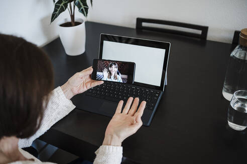 Woman with laptop gesturing while talking with daughter on video call through mobile phone at home - EBBF02582