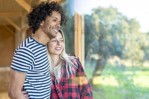 Smiling girlfriend standing with arm around boyfriend by window at front yard - SBOF02784
