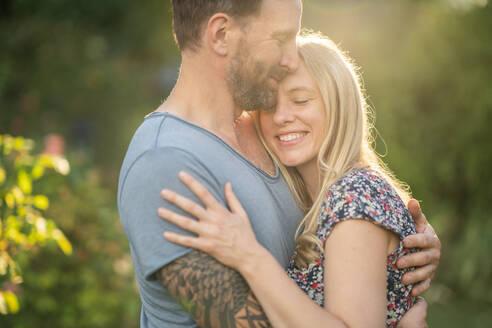 Deutschland, Hessen, Münzenberg, Paar umarmt sich im eigenen Garten, Eigenheim, Selbstverwirklichung, Beziehung, Liebe, Mann und Frau - AKLF00098