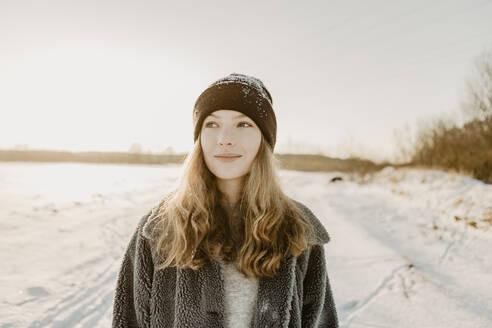 Deutschland, Brandenburg, Strausberg, Portrait von lachendem Mädchen in verschneiter Winterlandschaft, Gegenlicht - OJF00434