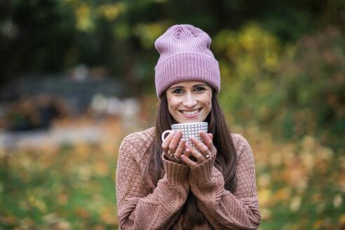 Deutschland, Hessen, Wiesbaden, junge Frau hält Teetasse in der Hand im Garten, Gesundheit, Achtsamkeit - AKLF00116